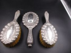 A TIFFANY AND CO STERLING THREE PART VANITY SET, HAND CHASED WITH REPOUSSE DECORATION AND A