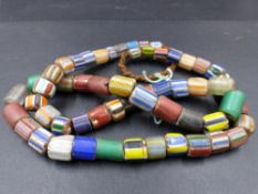 A GRADUATED ROW OF ANTIQUE GLASS AND HARDSTONE TRIBAL CYLINDRICAL TRADE BEADS, LENGTH 80cms.