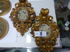 A PAIR OF ITALIAN CARVED GILTWOOD ROCOCO STYLE OVAL MINIATURE FRAMES. H.29cms. TOGETHER WITH TWO