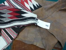 AN AMERICAN INDIAN PIECED LEATHER TRIBAL BLANKET WITH BRAIDED FRINGE AND A NAVAJO MAT WITH GEOMETRIC