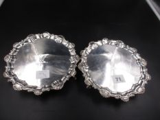 A NEAR PAIR OF GEORGIAN SILVER SALVERS WITH A SCROLLING SHELL PATTERN RIM, A CREST ENGRAVED CENTRE