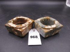 TWO SIMILAR MOTTLED BROWN AND GREY HARDSTONE CONGS VARIOUSLY CALCINED, THE CYLINDRICAL HOLES