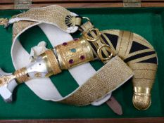 A MIDDLE EASTERN JAMBIYA KNIFE .YELLOW METAL MOUNTED AND INSET WITH SEMI PRECIOUS STONES