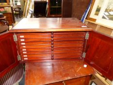 A VICTORIAN MAHOGANY COIN COLLECTOR'S CABINET WITH PANEL DOORS ENCLOSING NINE COIN SLIDES. 49 x 34 x
