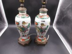 A PAIR OF FAMILLE VERTE CHINESE BALUSTER VASES WITH ORMOLU, MOUNTED AS LAMPS, WARRIOR DECORATION.