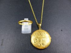 AN 18ct GOLD LOCKET AND CHAIN TOGETHER WITH A 22ct WEDDNG BAND. MEASURMENT OF LOCKET 3.1cms ROUND,