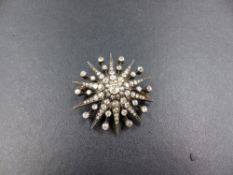 AN ANTIQUE OLD CUT DIAMOND STARBURST BROOCH SET IN SILVER OVER GOLD AND TESTED. THE CENTRAL