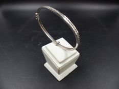 AN 18ct WHITE GOLD AND DIAMOND CHANNEL SET HINGED BANGLE. THE CHANNEL OF DIAMONDS ARE BRILLIANT