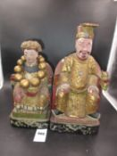 A PAIR OF CHINESE LACQUERED WOOD FIGURES OF AN EMPEROR AND EMPRESS SEATED ON RED THRONES DRAPED WITH