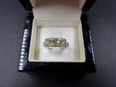 AN 18ct WHITE GOLD GREEN SAPPHIRE AND DIAMOND DRESS RING. PRINCESS CUT GREEN SAPPHIRES ARE IN A