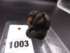 A JAPANESE CARVED WOOD FIGURE OF A SEATED MONKEY HOLDING A BUNCH OF GRAPES, SIGNED. H.4cms.