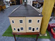 A VINTAGE PAINTED PINE COUNTRY HOUSE DOLL'S HOUSE RAISED ON A VICTORIAN MAHOGANY TURNED LEG STAND.