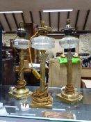 THREE BRASS CORINTHIAN COLUMN OIL LAMPS WITH GLASS RESERVOIRS CONVERTED FOR ELECTRICITY. (3)