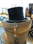 A VINTAGE MOSS BROS. BLACK SILK TOP HAT IN A PERIOD CANVAS HAT BOX, NO SIZE NOTED BUT INTERNAL RIM
