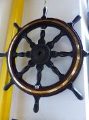 AN ANTIQUE MAHOGANY AND BRASS MOUNTED SHIP'S WHEEL WITH IRON CENTRAL BOSS. Dia.92cms TOGETHER WITH A