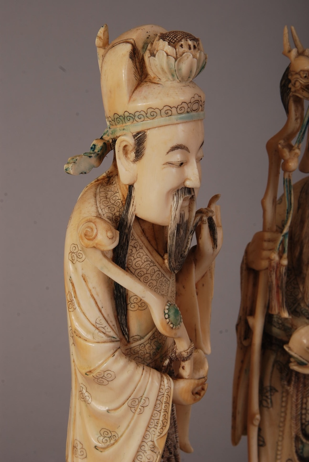 Lot 54 - Set of three C18th/19th Chinese ivory figures of immortals, the first holding a fruiting peach and a