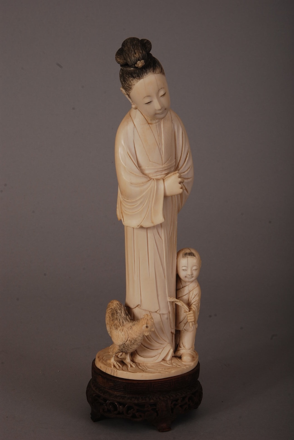 Lot 53 - C18th/19th Chinese ivory figure group of a lady and a boy, 26.5cm high, wood stand