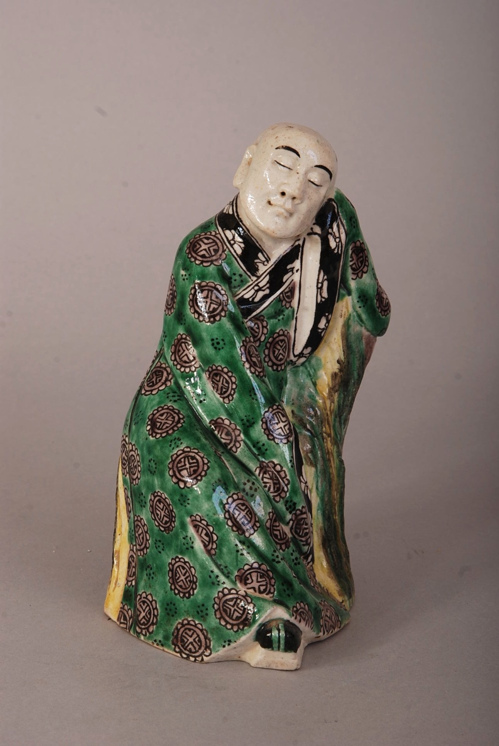 Lot 59 - C19th Chinese sancai figure of Luohan, resting on a chair and wearing long robes, impressed seal
