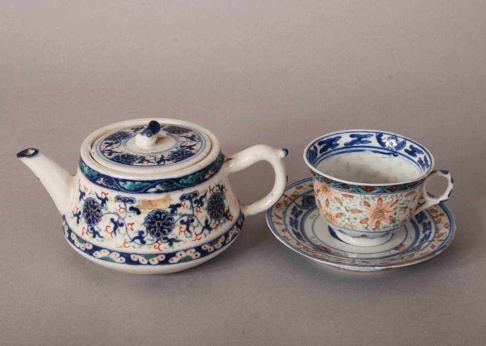 Lot 23 - C19th Chinese iron-red and blue and white teapot and cover, painted with scrolling lotus, Qianlong