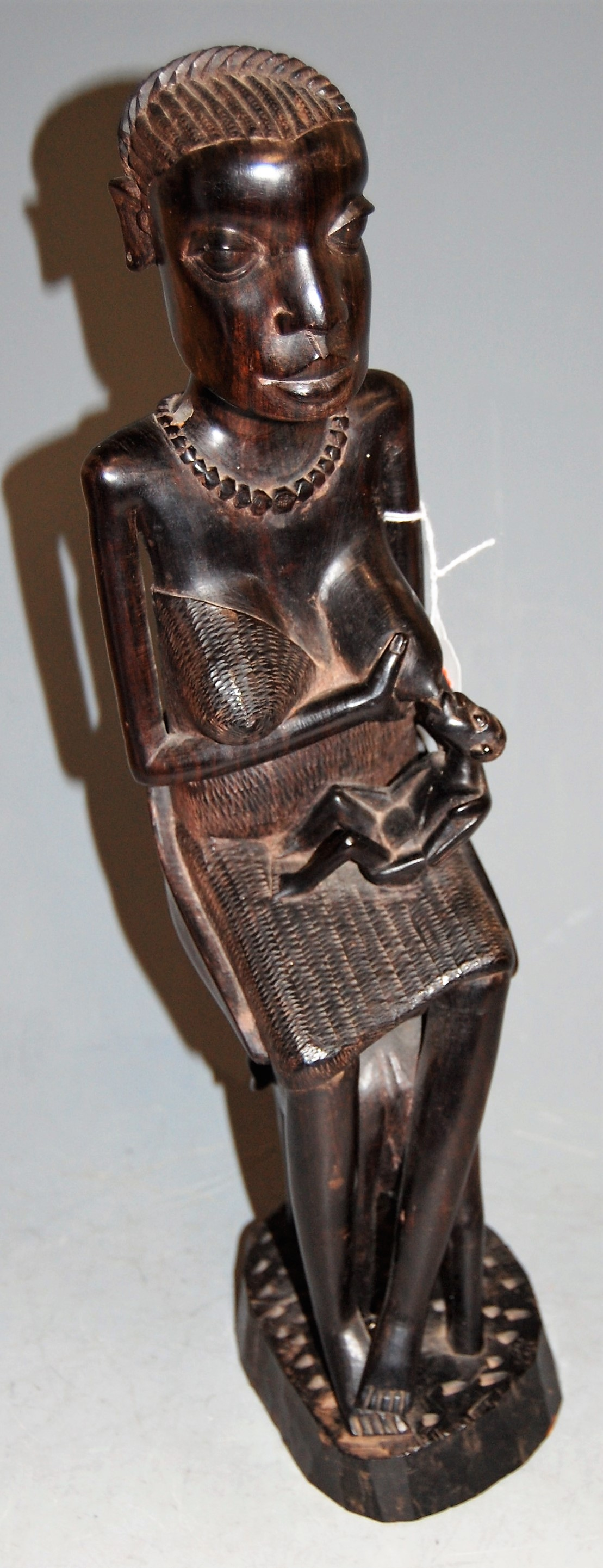 Lot 14 - An African carved ebony fertility figure in the form of a nursing woman, h.45cm