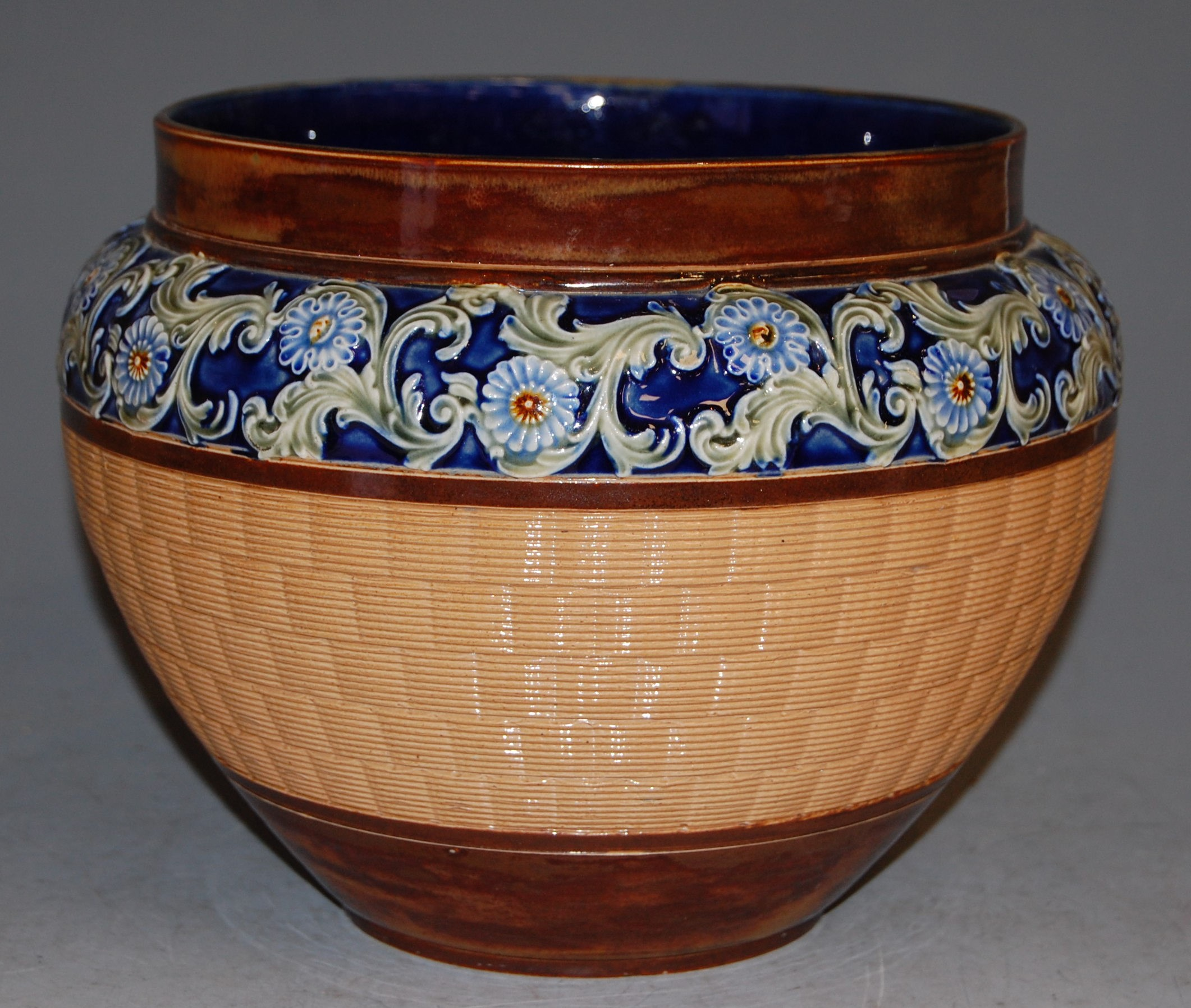 Lot 27 - An early 20th century Doulton Lambeth stoneware jardinière, having basket weave body and floral