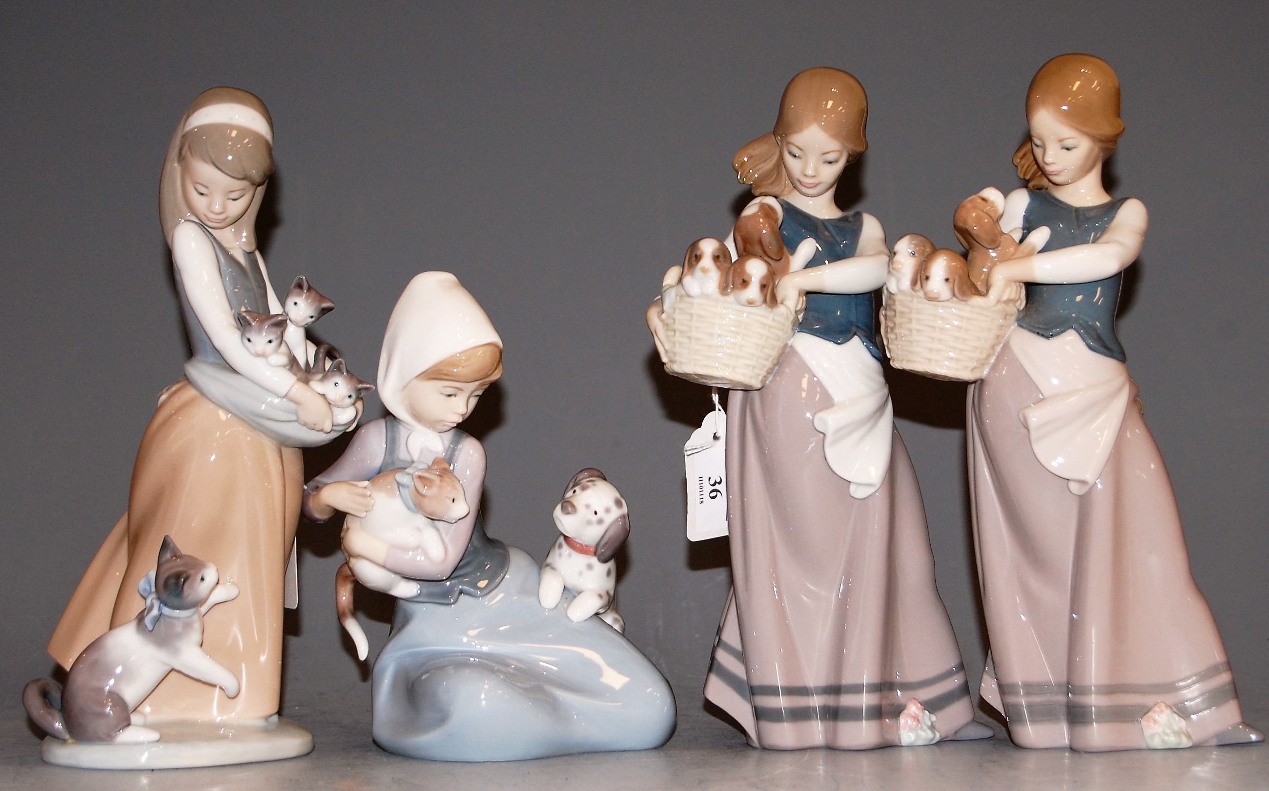 Lot 36 - A Lladro figure of a girl in standing pose with a basket and puppies, 24cm; together with three