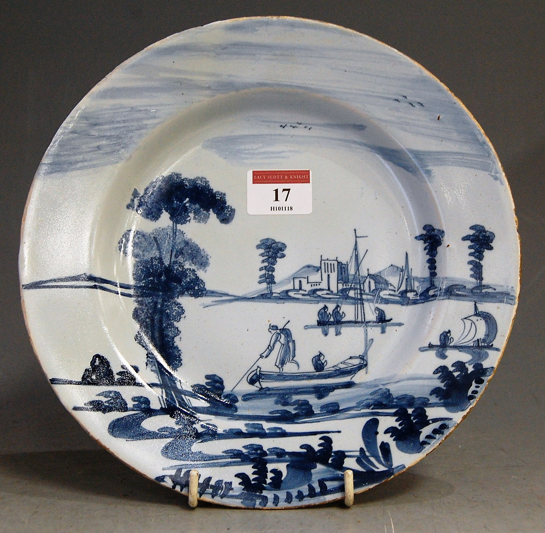 Lot 17 - An 18th century Dutch delft blue and white plate, depicting figures amidst river landscape (