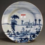 Lot 17 - An 18th century Dutch delft blue and white plate, depicting figures amidst river landscape (