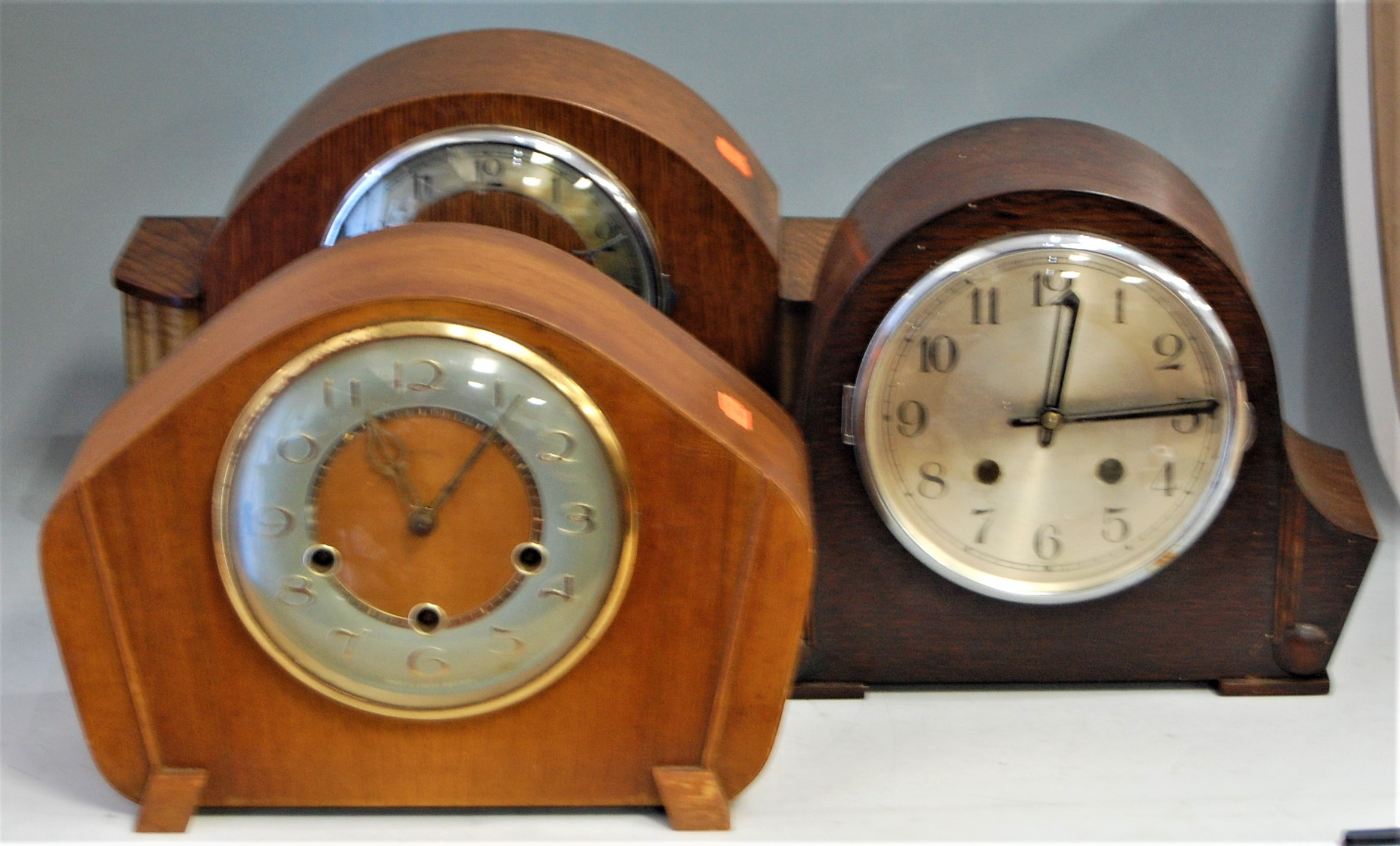 Lot 21 - An Art Deco oak cased mantel clock, having silvered chapter ring with Arabic numerals and chiming
