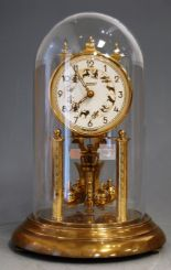 Lot 49 - A German lacquered brass anniversary clock under glass dome, h.30cm