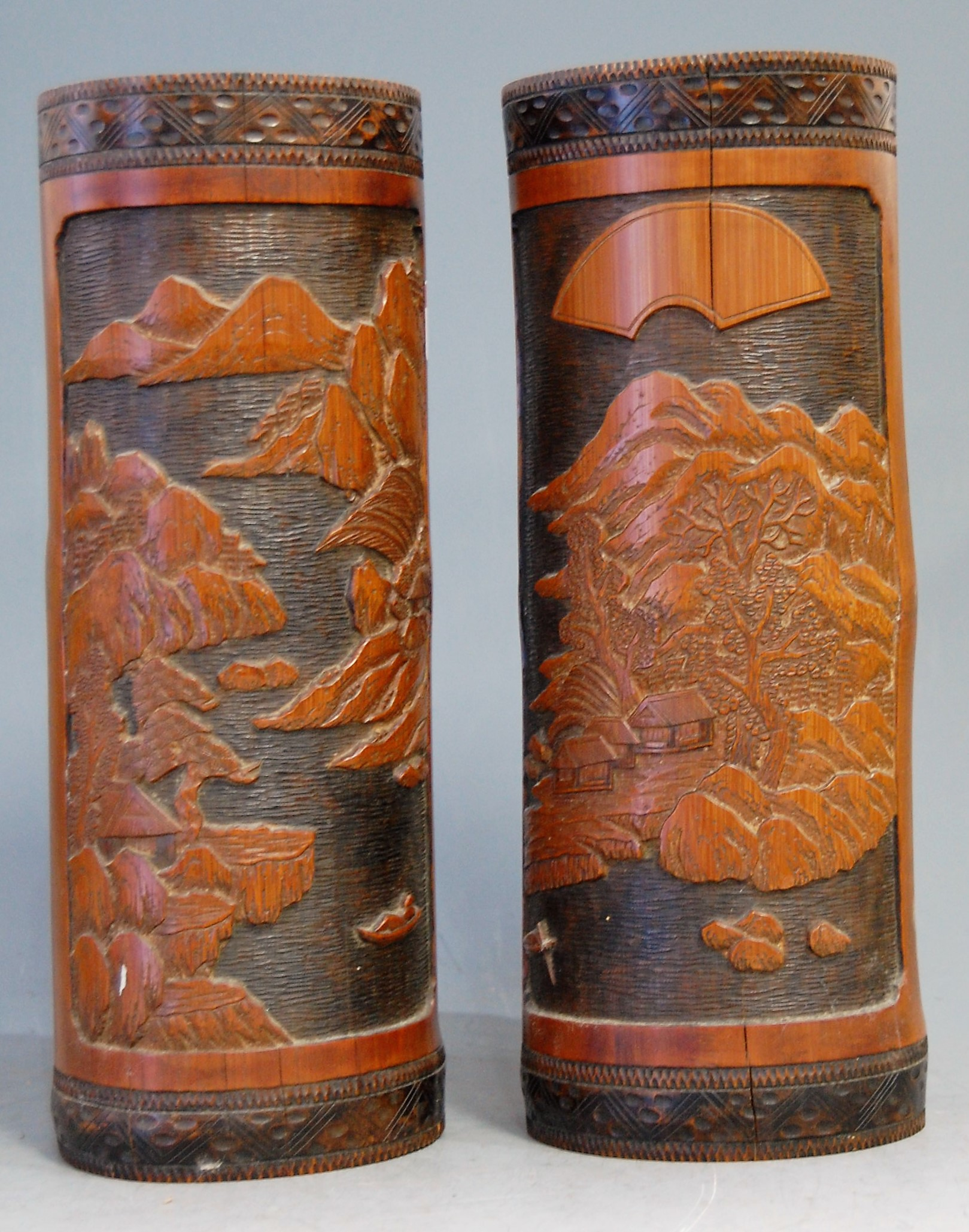 Lot 31 - A pair of mid-20th century Chinese brush pots, each carved with mountain landscape scene, h.29cm