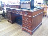 Lot 5 - A reproduction mahogany desk, the leather top over three frieze drawers on pedestals each with three