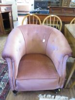 Lot 36 - A pink upholstered tub armchair, with turned feet and castors