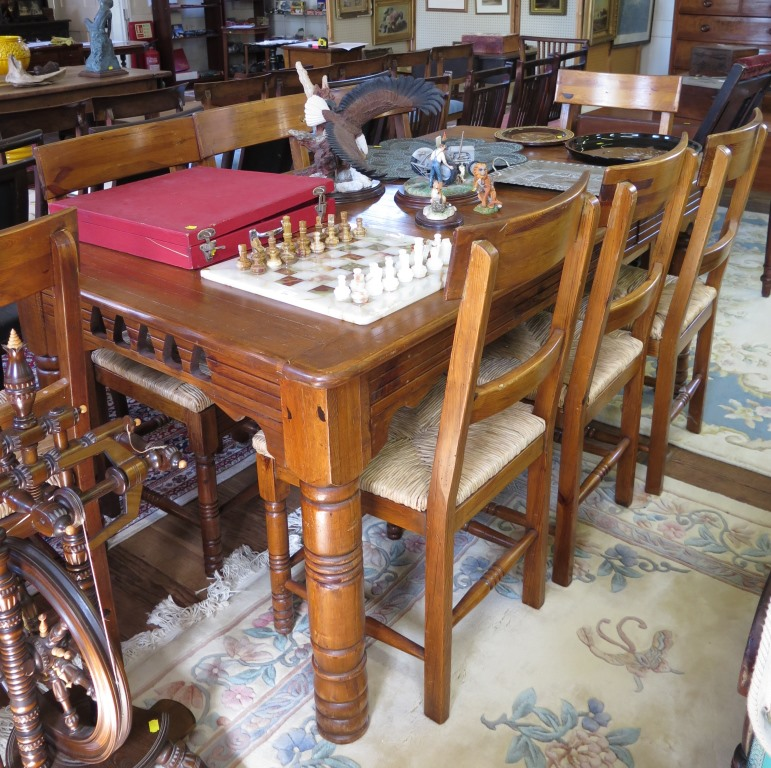 Lot 52 - A stained pine dining table and eight chairs by Dixy, the table with frieze drawer 180cm x 100cm,