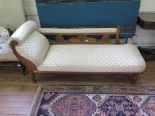 Lot 32 - An Edwardian beech chaise longue, with scroll arm and floral carved back on turned legs