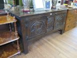 Lot 58 - An oak side cabinet, in the form of a coffer, the doors carved with a king and queen flanking a
