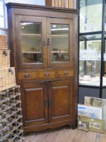 Lot 28 - An early 20th century corner cabinet, with twin glazed doors over three drawers and a pair of
