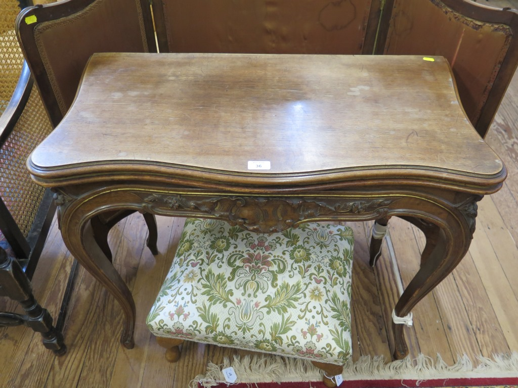 Lot 36 - A late 19th century French parcel gilt foldover card table, the shaped top over a foliate carved