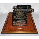 Schreibmaschine Triumph Nr. 116115, auf Holz montiert mit Holzrahmen, H 28 cm, B 58 cm T 63 cm,