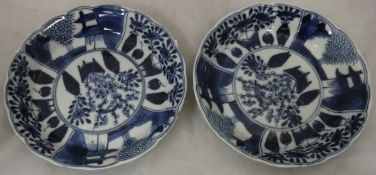 A pair of Chinese blue and white saucer dishes decorated with panels of interior and garden scenes,