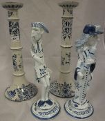 A pair of early 20th Century Dutch Delft candlesticks of cylindrical ringed form decorated with