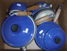 A box containing five blue enamel Le Creuset saucepans and a white cast iron pan stand