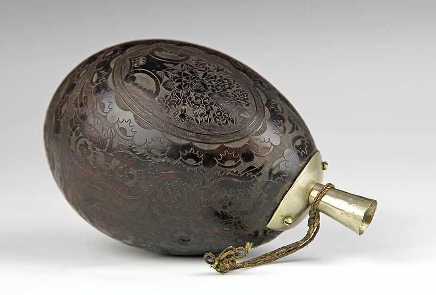 Lot 47 - Nautik - - Beschnitzte Kokosnuss als Pulverhorn. Französische Kolonialarbeit um 1800, reich graviert