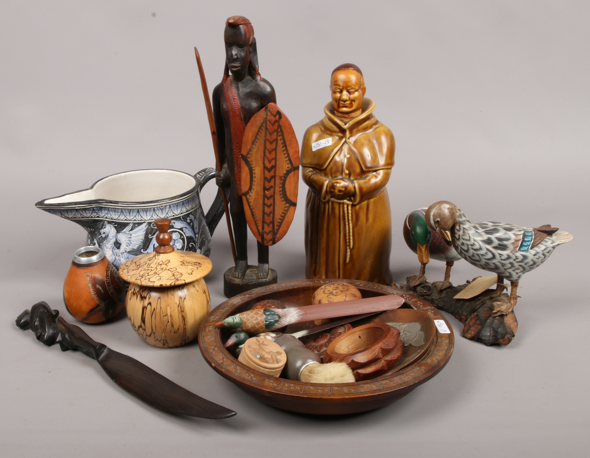 Lot 32 - A continental tin glazed jug, Monk formed Whisky decanter, African carved wood tribal figure, hand