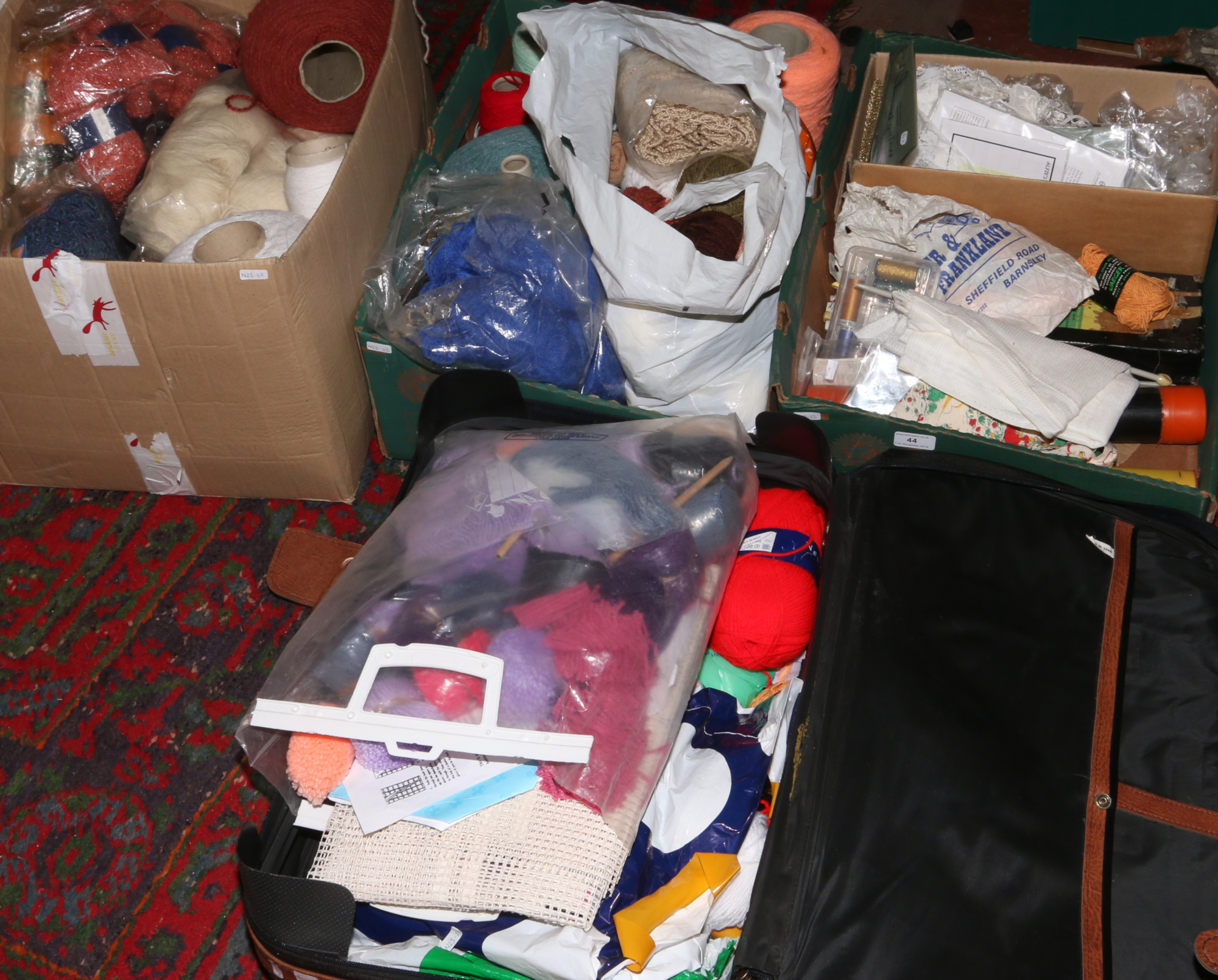 Lot 44 - Three boxes and a suitcase of sewing and knitting equipment to include a large quantity of wool