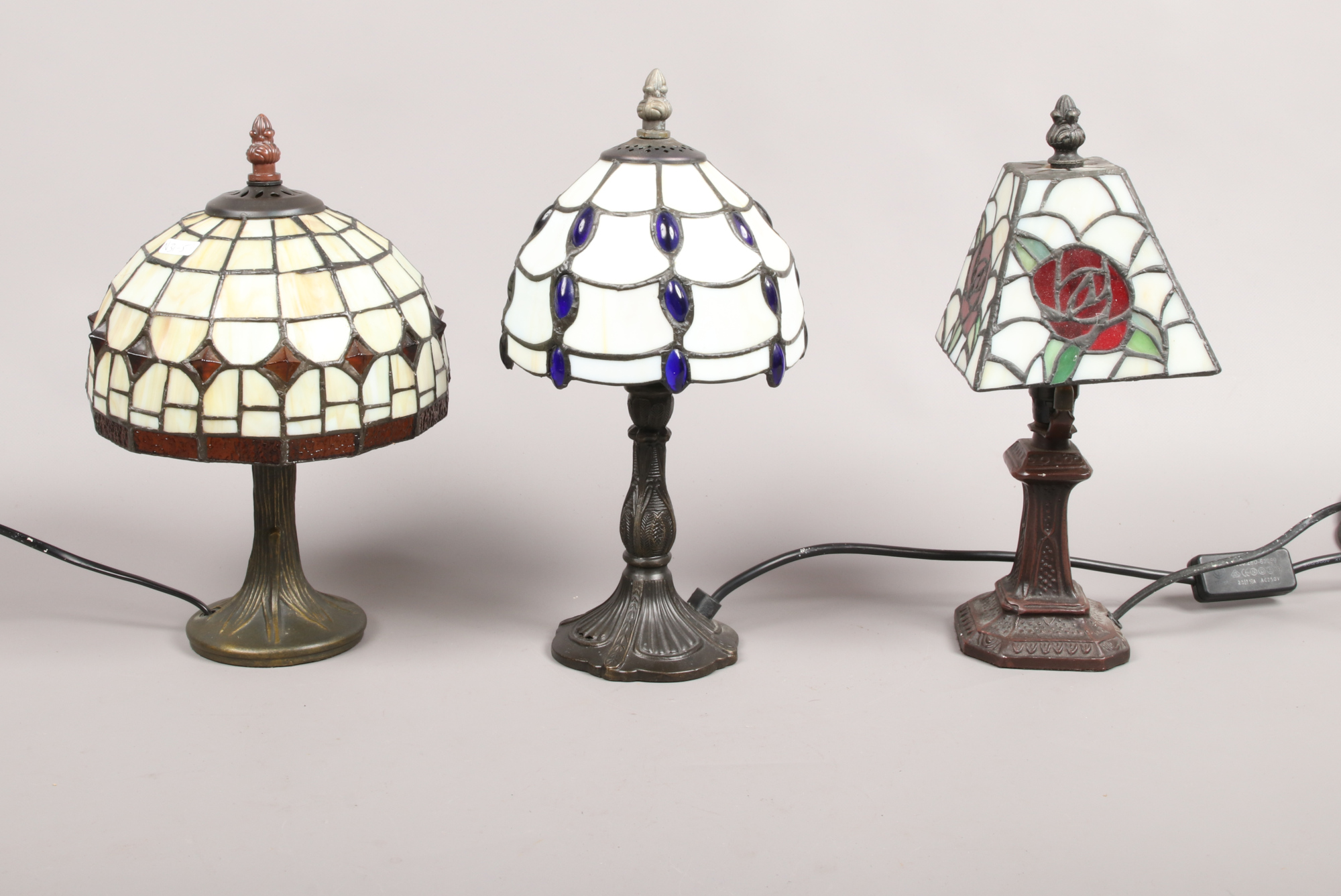 Lot 56 - Three small Tiffany style leaded and coloured glass table lamps.