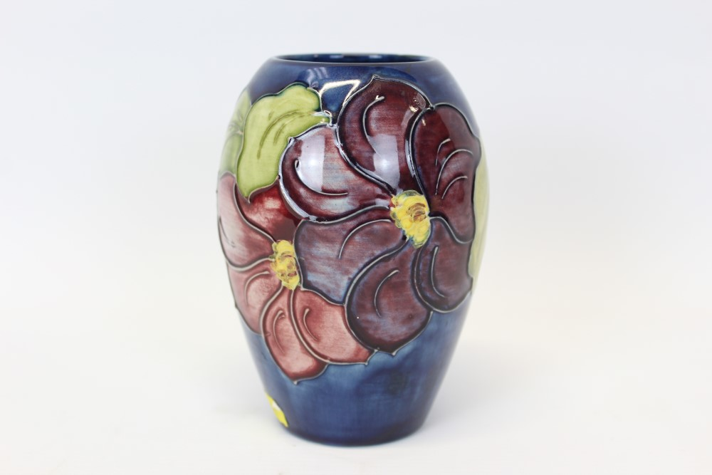 Lot 2010 - Moorcroft pottery vase decorated in the Hibiscus pattern on blue ground,