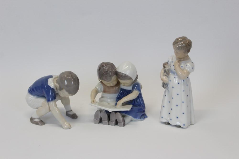 Lot 2043 - Royal Copenhagen porcelain figure - girl holding doll,