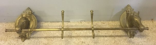A cast brass coat hook rail The wall supports horses' heads. 76 cm wide.