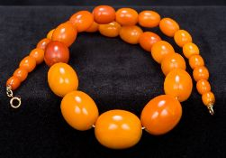 An amber bead necklace The beads of graduated form, mounted with a gold clasp. 44 cm long.